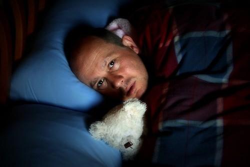 Мужчина в постели с плюшевым мишкой