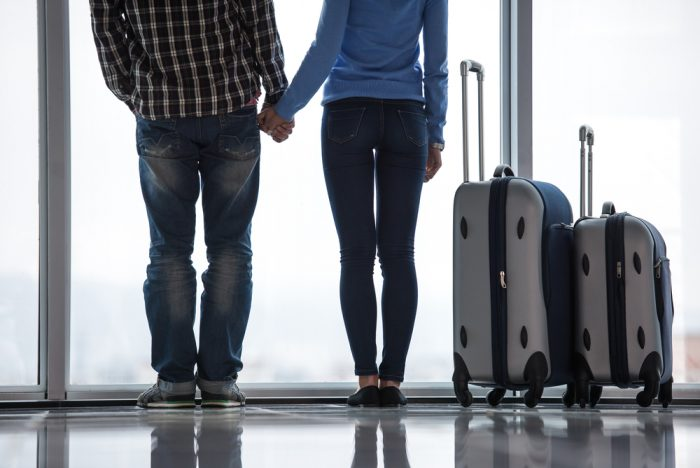 Девушка с парнем Держутся за руки возле чемоданов