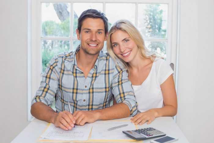 Мужчина и женщина сидят за столом с бумагами и скалькулятором