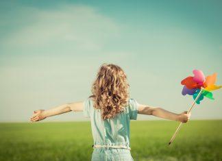 Девочка на открытом воздухе с игрушкой в руке