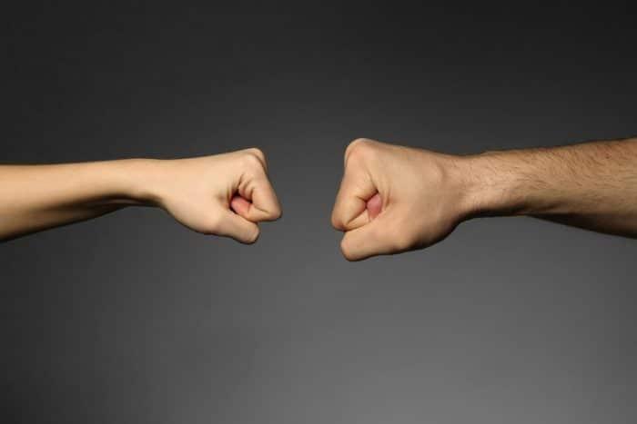 Мужской и женский кулак на сером фоне