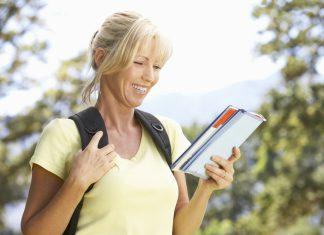 Женщина на природе с рюкзаком и с блокнотом