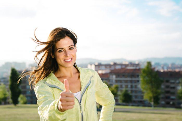 Женщина в зеленой ветровке показывает класс
