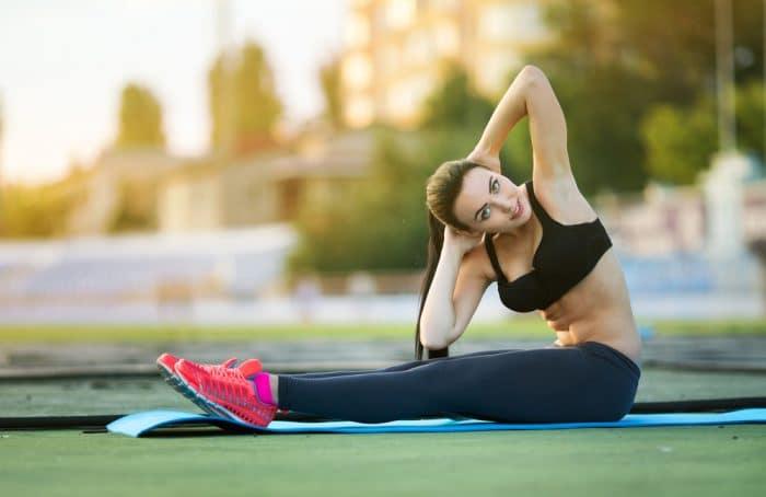 Девушка на природе на коврике делает упражнения
