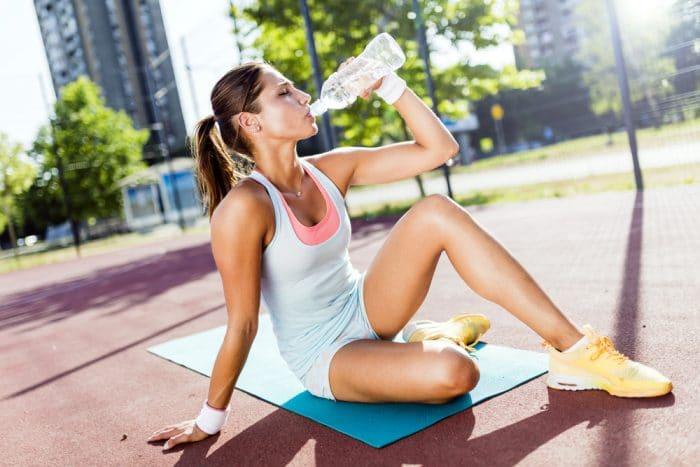 Девушка на улице, сидя на коврике пьет воду