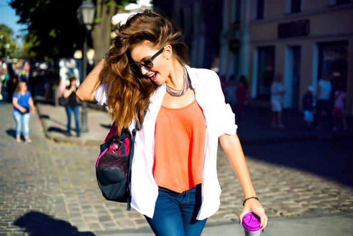 Девушка в очках и с красной помадой идет с спортивно умкой