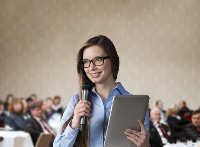 Девушка с микрофоном и в очках выступает