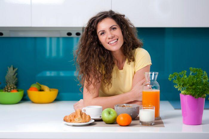 Девушка сидит перед столом с графином сока, стаканом молока и завтраком