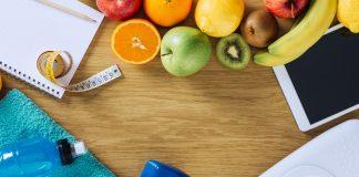 Гантели, блокнот, вода,фрукты, весы, планшет на деревянном столе