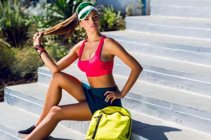 Спортивная девушка с рюкзаком сидит на ступеньках