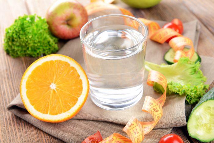 Стакан воды, половина апельсина, листья салата и сантиметр на столе