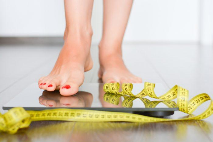 Женская нога становится на весы с сантиметром