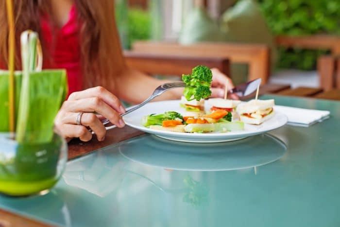 Женские руки жержат вилку с ножом над тарелкой салата
