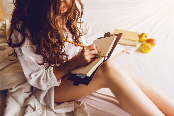 Девушка делает заметки в дневнике