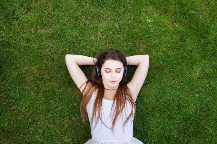 Девушка лежит на траве и слушает музыку в наушниках