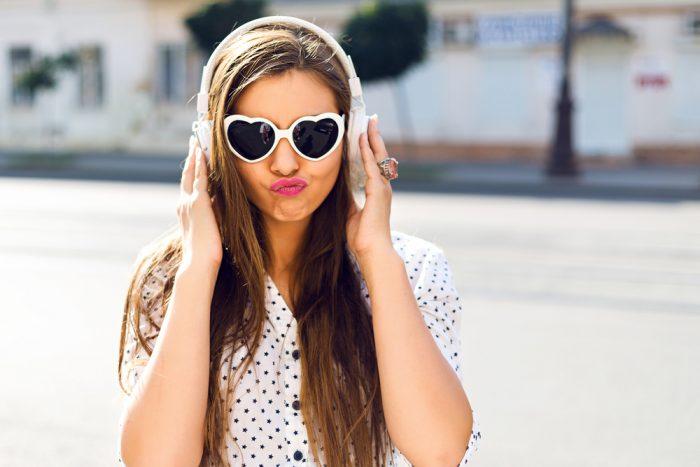 Девушка в белых очках серце и в наушниках