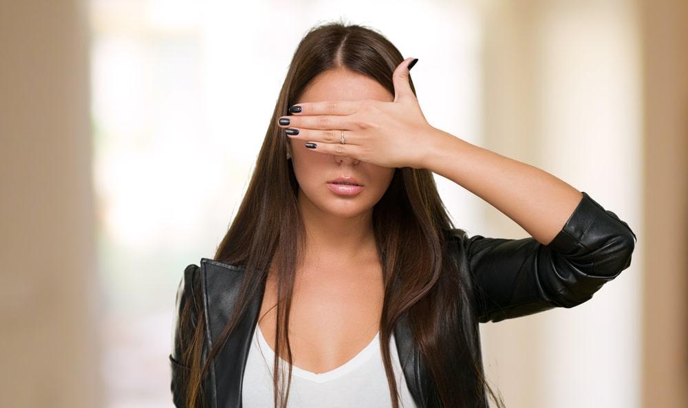 Девушка в кожаной куртке закрыла глаза рукой