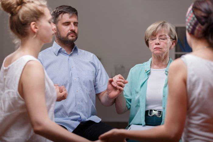 Люди сидя в кругу держатся за руки во время терапии