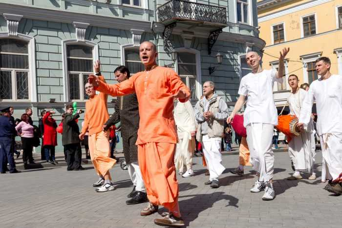 Люди в оранжевых и белых костюмах поют и танцуют на улице