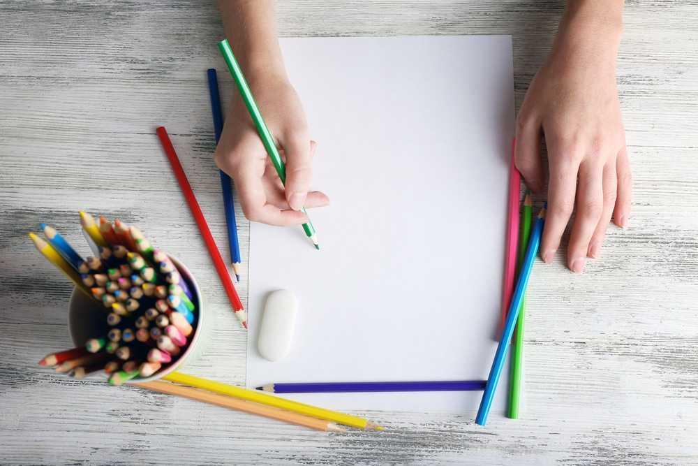 Руки с цветными карандашами и пустой лист бумаги на деревянном столе