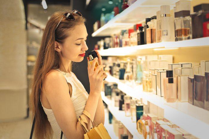 Девушка в парфюмерном магазине нюхает парфюм