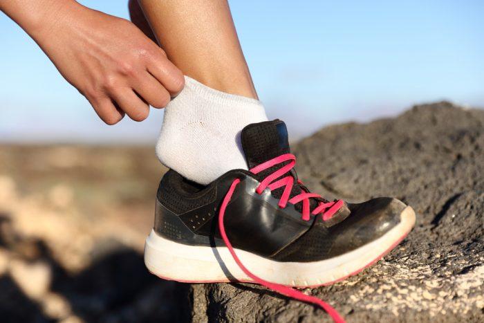 Надевает кроссовок на ногу на камне