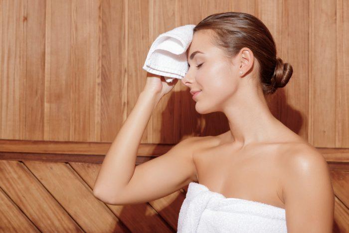 Девушка с белым полотенцем в сауне