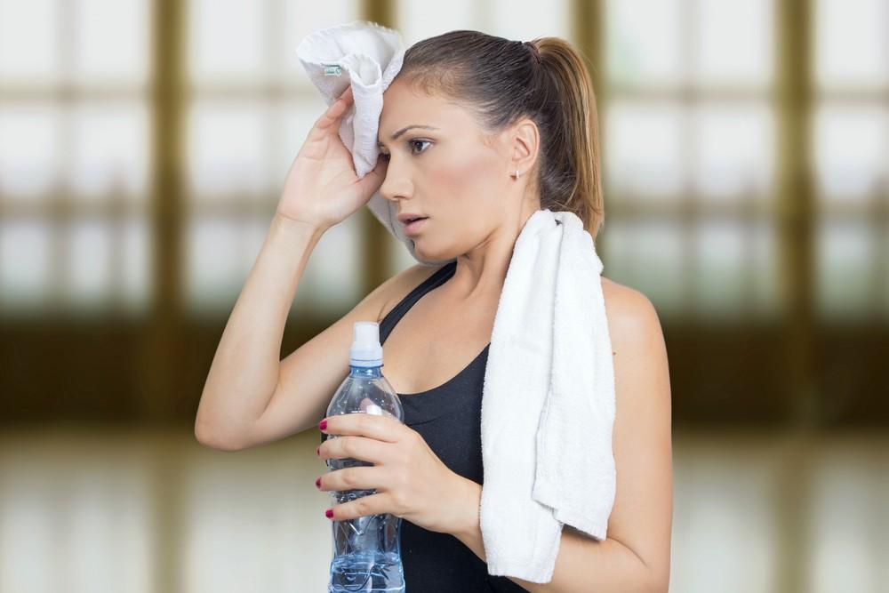 Девушка с бутылкой в руках вытирает лоб полотенцем