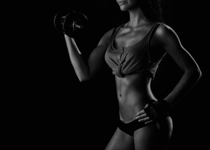 Спортивная девушка в черном топике и коротких шортах держит гирьку