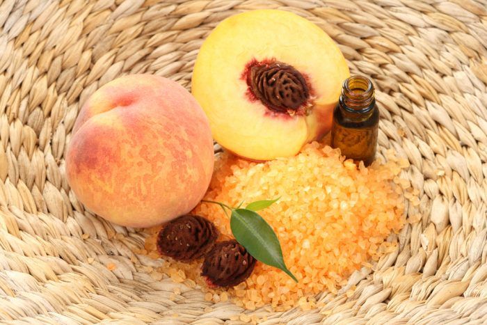 Персик в корзине с бутылочкой масла и морской солью