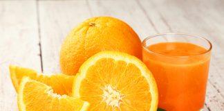 Стакан сока с апельсинами на столе