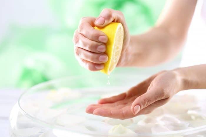 Женские руки давят сок из половины лимона