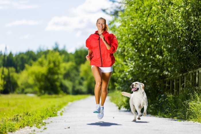 Женщина напробежке с собакой