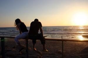 Парень с девушкой сидят на пляже на закате
