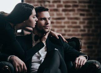 Девушка целует мужчину сидящего в кресле