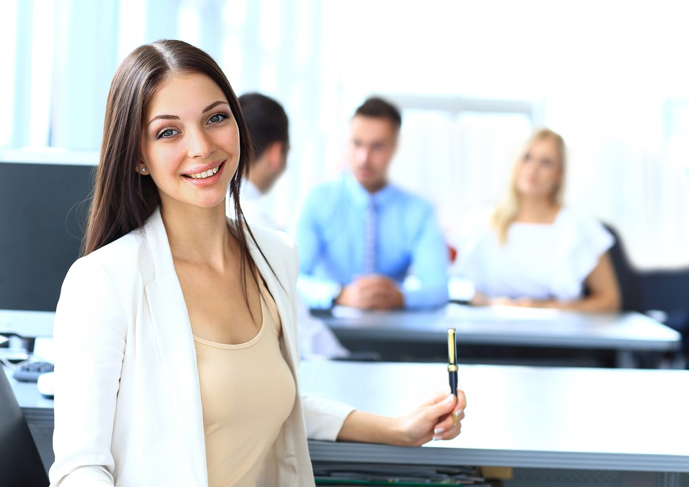 Девушка в белом пиджаке держит ручку