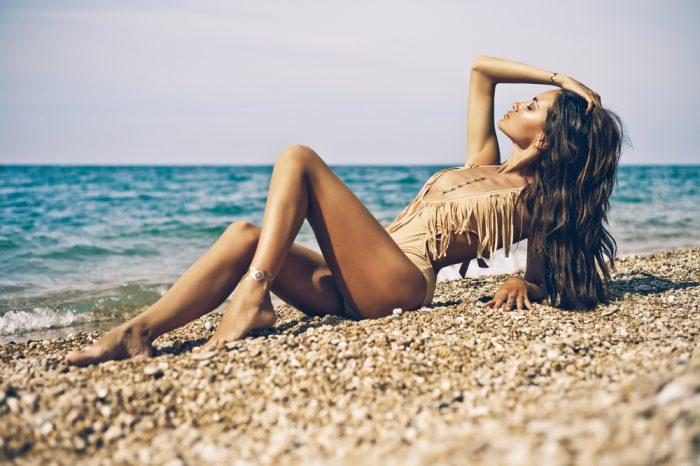Девушка в бежевом купальнике загорает на пляже