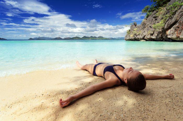 девушка в черном купальнике лежит на берегу океана
