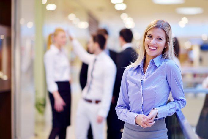 Девушка в голубой рубашке улыбается на фоне людей