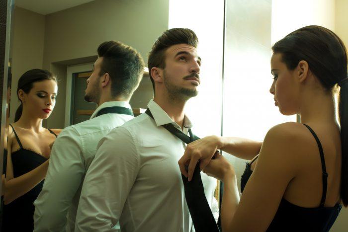 Девушка завязывает галстук мужчине