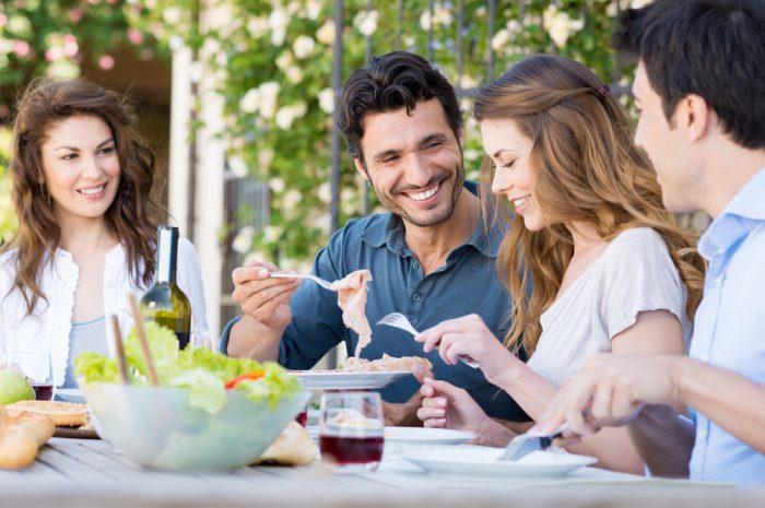 Две пары обедают и улыбаются