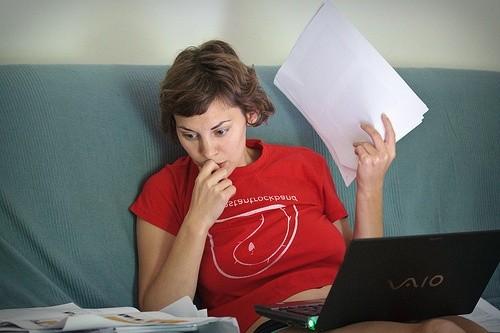 Женщина с бумагами и ноутбуком