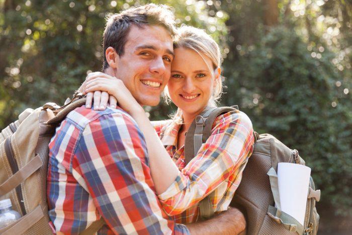 Парень с девушкой в клетчатых рубашках с рюкзаками обняли друг друга