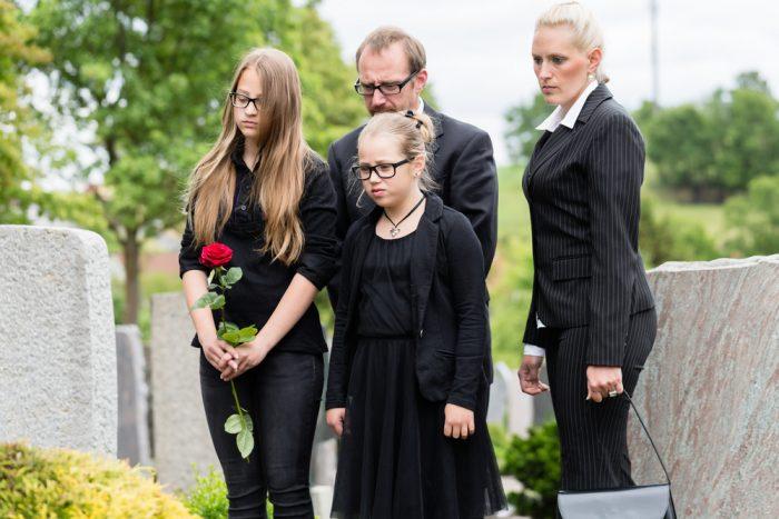 Семья в черной одежде на похороне