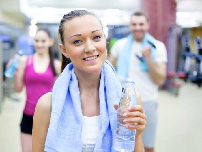 Девушка с полотенцем и бутылкой воды на тренировке