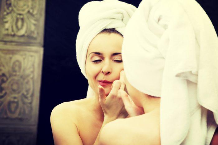 Девушка перед зеркалом с полотенцем на голове