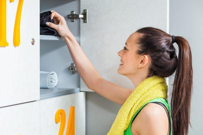Девушка с желтым полотенцем открыла свой шкафчик в раздевалке