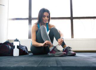 Девушка сидит на полу и завязывает шнурки на кроссовках