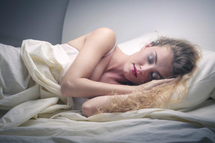 Девушка спит на белой постели
