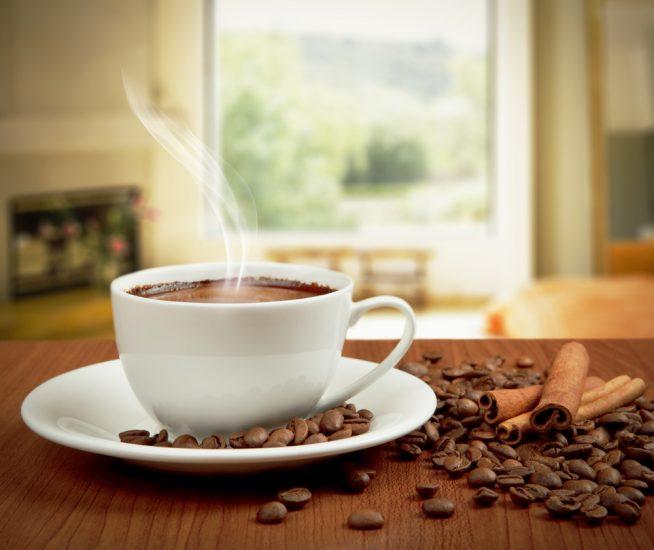 Чашка кофе на столе в зернах и палочкой корицы